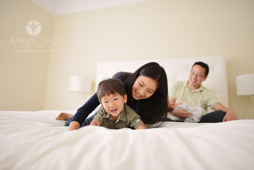 San-Francisco-lifestyle-newborn-family-photography-mother-playing-with-toddler-while-father-holds-baby-in-background