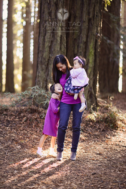 East-Bay-lifestyle-family-photography-mother-hugging-her-daughters-in-forest-with-streaming-light