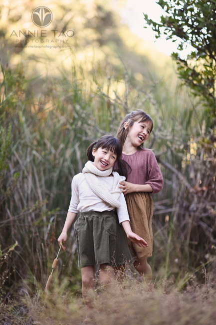 Bay-Area-lifestyle-children-photography-two-sisters-laughing-while-hugging-in-fuzzy-bush