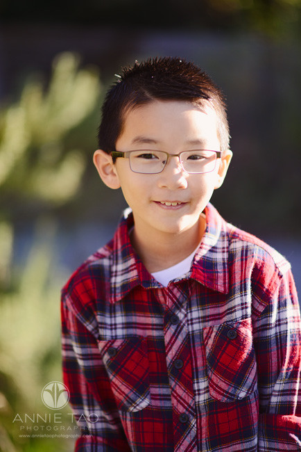 East-Bay-children-lifestyle-photography-young-boy-with-glasses-by-bush