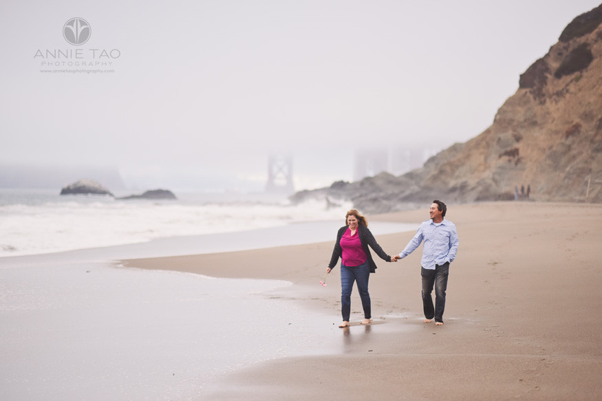 San-Francisco-engagement-photography-couple-walking-on-beach-by-golden-gate-bridge