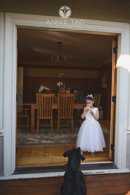 East-Bay-lifestyle-children-photography-girl-eating-cheese-and-watching-dog-in-doorway
