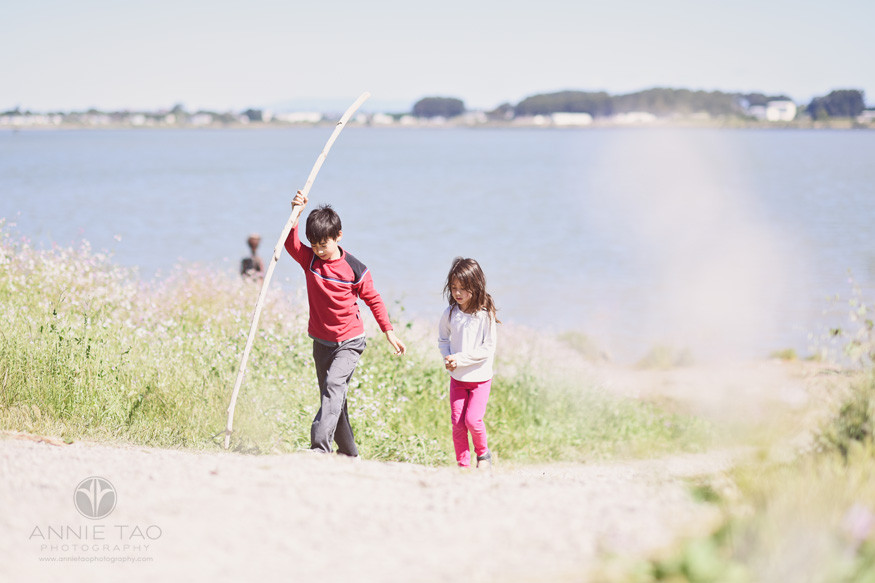 East-Bay-lifestyle-children-photography-young-siblings-walking-with-sticks-up-a-hill