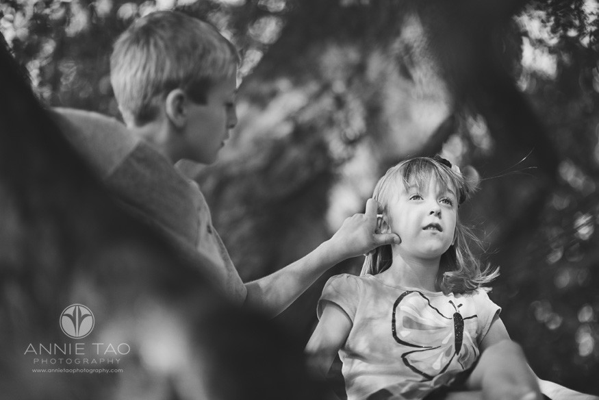 East-Bay-lifestyle-children-photography-big-brother-fixing-little-sisters-hair-while-sitting-in-a-tree-BxW