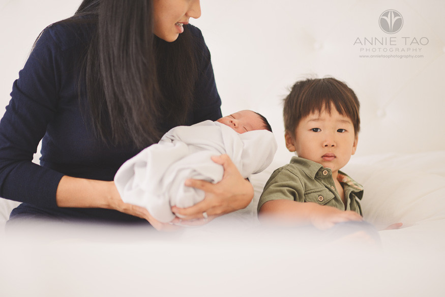 San-Francisco-lifestyle-newborn-family-photography-mother-holding-baby-and-looking-at-toddler-son-in-a-white-cloud