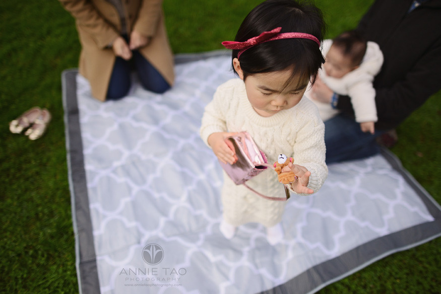 Bay-Area-Palo-Alto-lifestyle-family-photography-toddler-girl-checking-out-purse-contents-while-family-on-picnic-blanket