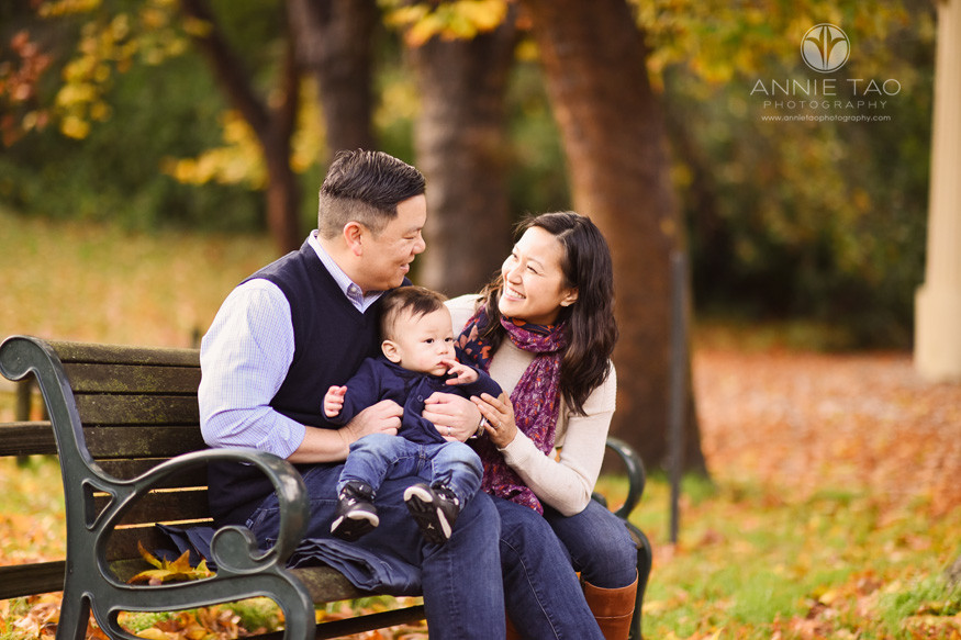 San-Francisco-lifestyle-baby-photography-parents-smiling-at-each-other-while-holding-baby-in-park-with-fall-leaves