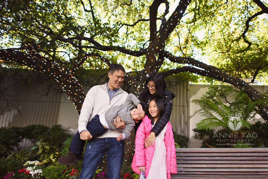 San-Francisco-lifestyle-family-photography-parents-hugging-and-holding-their-young-children-under-tree-with-holiday-lights