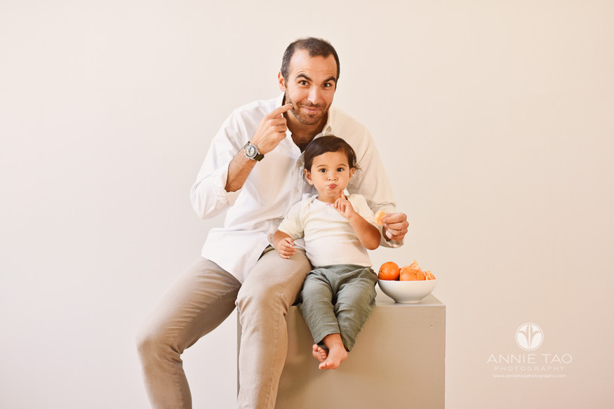 East-Bay-commercial-photography-father-and-baby-pointing-at-cheeks-while-eating-mandarin-oranges