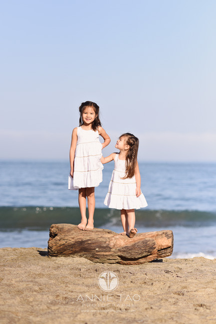 San-Francisco-lifestyle-children-photography-little-sister-looking-up-at-big-sister-on-log-at-beach