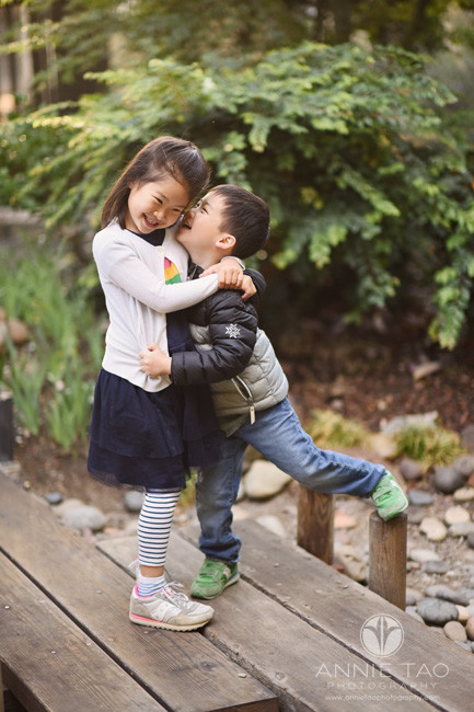 Bay-Area-lifestyle-children-photography-siblings-hugging-and-whispering-to-each-other-on-wooden-footbridge