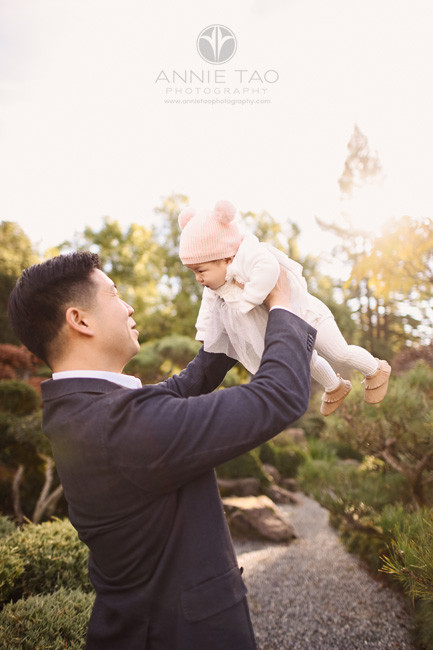 east-bay-lifestyle-baby-photography-father-holding-up-baby-girl-in-garden