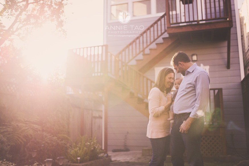 san-francisco-lifestyle-family-photography-parents-laughing-while-holding-baby-in-backyard-with-sunflare