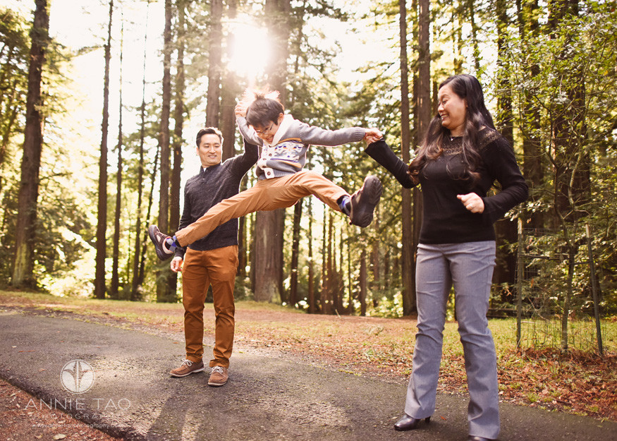 East-Bay-lifestyle-family-photography-young-boy-jumping-into-splits-with-parents-in-forest