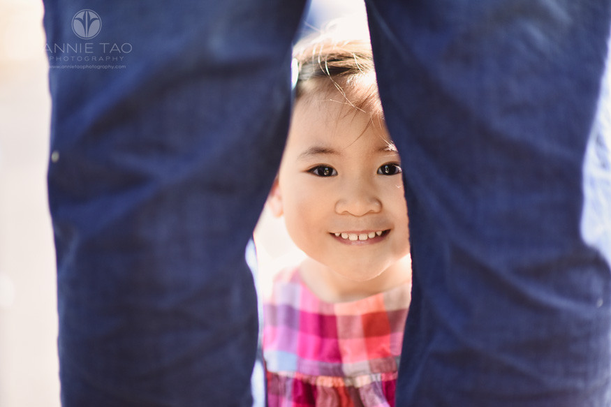 South-Bay-lifestyle-children-photography-smiling-toddler-girl-peeking-through-parents-legs