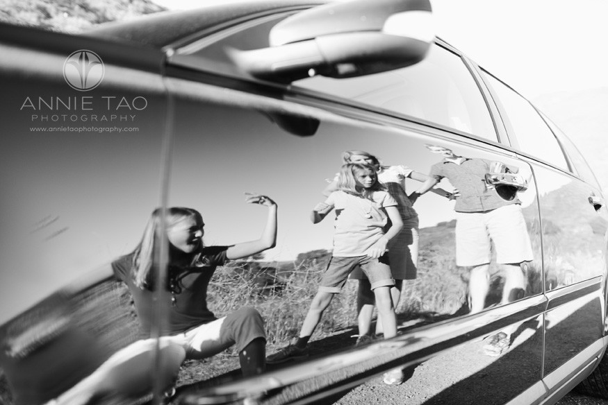 East-Bay-lifestyle-family-photography-checking-out-the-reflection-on-the-side-of-a-black-car-BxW