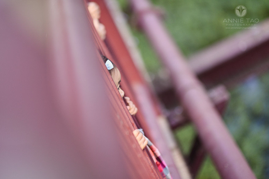 South-Bay-lifestyle-children-photography-kids-sticking-face-and-hands-through-slats-on-red-bridge