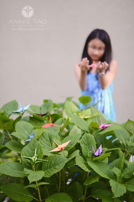 East-Bay-lifestyle-preteen-photography-girl-holding-origami-crane-behind-wishing-bush