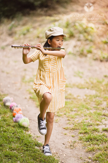 East-Bay-styled-children-photography-girl-marching-while-playing-flute-while-animals-follow-behind