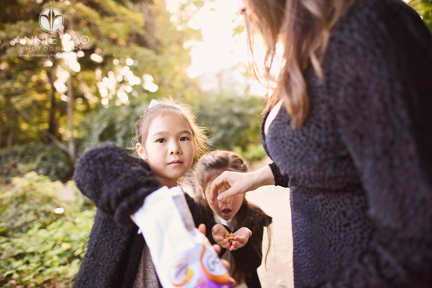 San-Francisco-lifestyle-children-photography-two-girls-grabbing-pretzel-snacks-from-mom