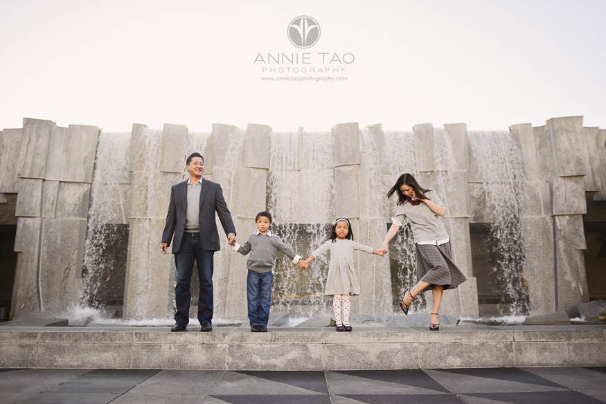 San-Francisco-lifestyle-family-photography-woman-checking-shoes-while-standing-with-family-by-waterfall