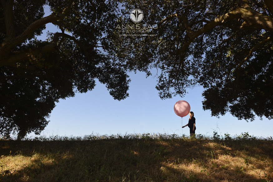 Bay-Area-lifestyle-maternity-photography-pregnant-woman-holding-giant-pink-balloon-surrounded-by-trees