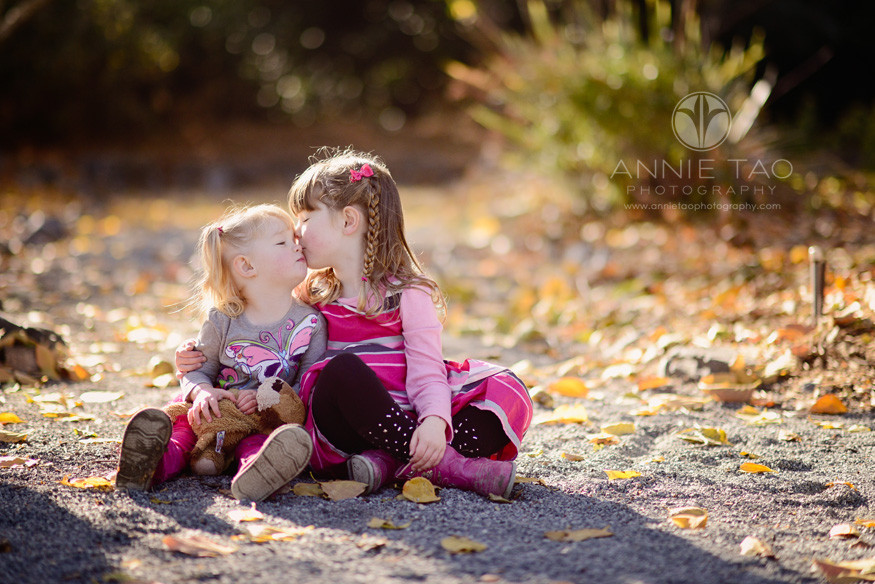 East-Bay-lifestyle-children-photography-sisters-in-shades-of-pink-sitting-among-leaves-and-kissing