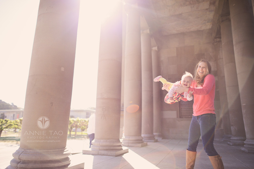 San-Francisco-lifestyle-family-photography-mother-playing-airplane-with-baby-by-columns-and-through-sunflare