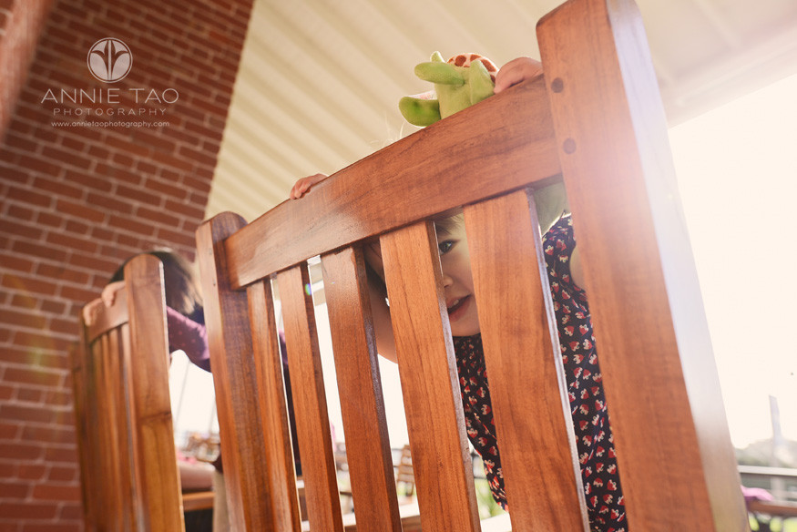 San-Francisco-lifestyle-children-photography-toddler-girl-peeking-through-chair-with-sunflare