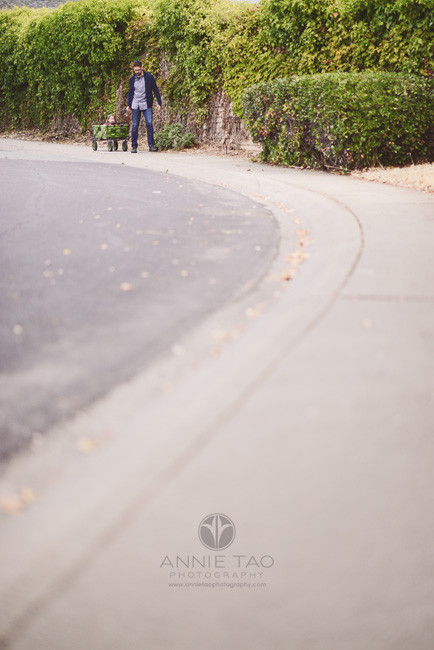East-Bay-lifestyle-family-photography-dad-pulling-toddler-daughter-in-wagon-on-path
