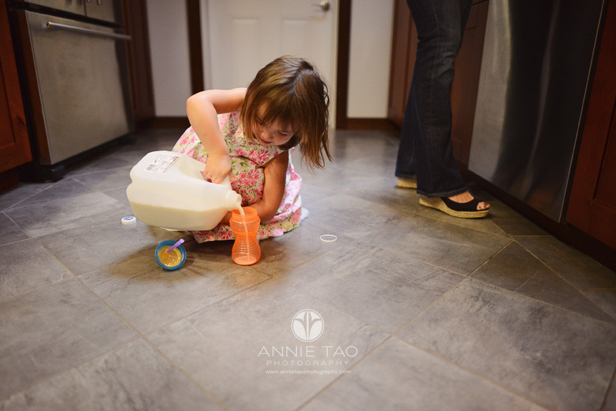 North-Bay-Marin-lifestyle-children-photography-toddler-girl-pouring-milk-into-sippy-cup-in-middle-of-kitchen-floor