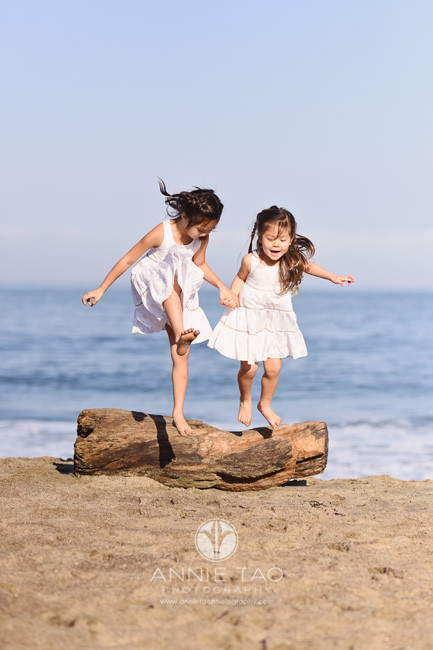 San-Francisco-lifestyle-children-photography-two-sisters-jumping-off-log-at-beach