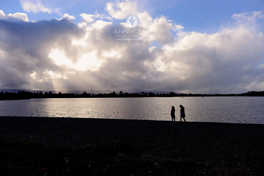 bay-area-lifestyle-children-photography-sisters-walking-along-edge-of-lake-after-the-rain-with-sunbeams-shining-through-clouds