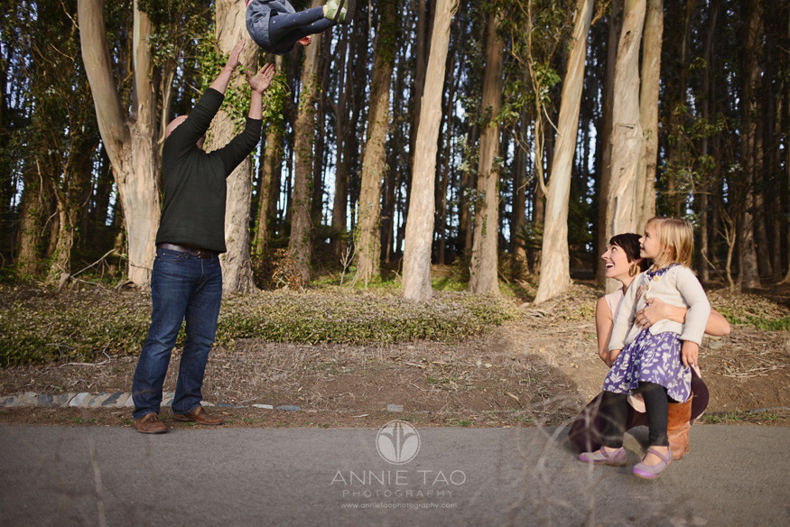 San-Francisco-lifestyle-family-photography-father-throwing-daughter-into-air-while-mother-and-youngest-daughter-look-on