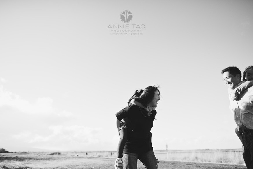 bay-area-lifestyle-family-photography-laughing-parents-giving-piggyback-rides-to-daughters-by-lake-bxw