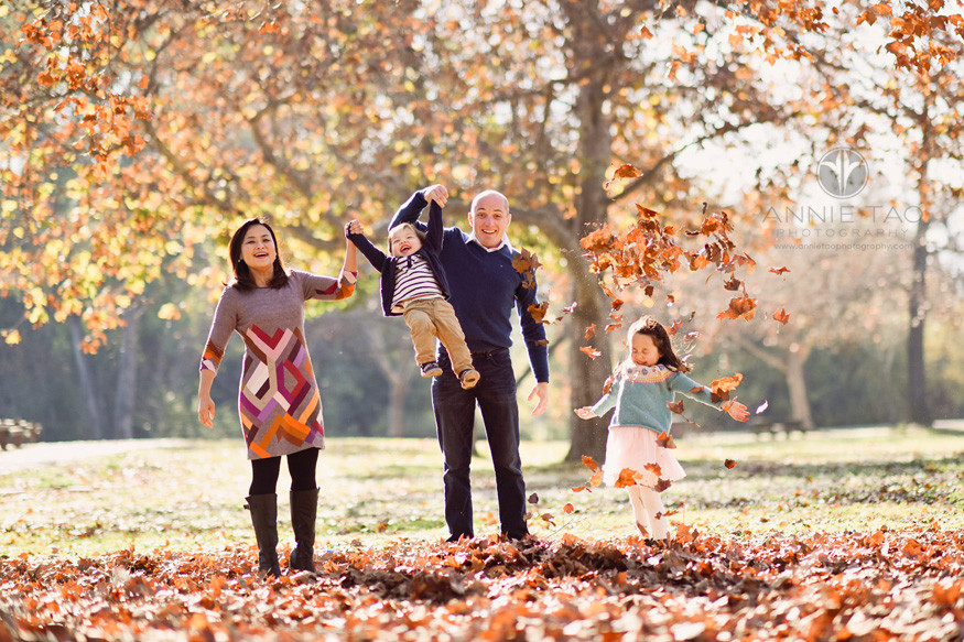 South-Bay-lifestyle-family-photography-parents-swinging-baby-while-preschooler-throws-autumn-leaves