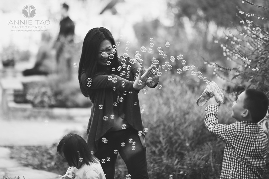 Bay-Area-lifestyle-family-photography-preschooler-son-blasting-mom-with-bubbles-in-garden-BxW