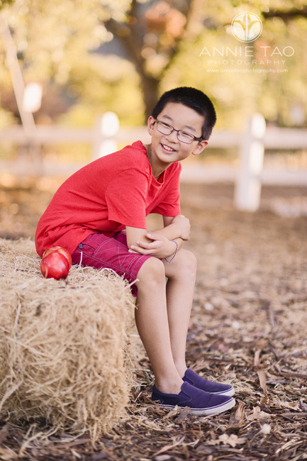 east-bay-styled-children-photography-boy-in-red-sitting-on-hay-with-apple