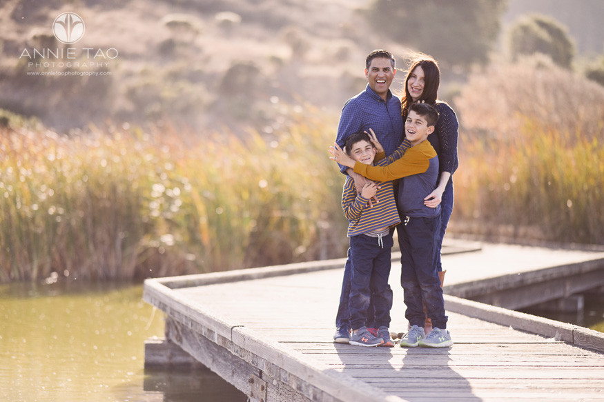 East-Bay-lifestyle-family-children-photography-brothers-giving-moose-ears-and-bunny-ears-to-each-other-while-standing-with-parents-on-boardwalk