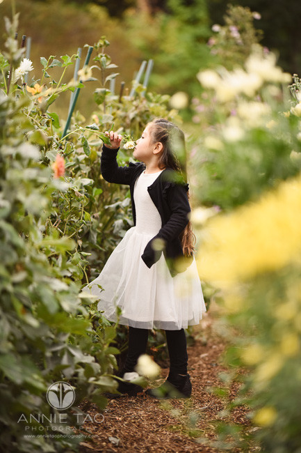 San-Francisco-lifestyle-children-photography-young-girl-reaching-to-smell-flower-in-garden