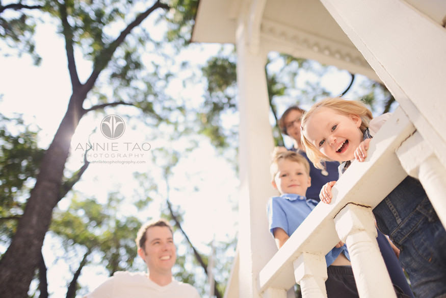 East-Bay-lifestyle-family-photography-family-watching-toddler-girl-lean-onto-railing-with-sunflare