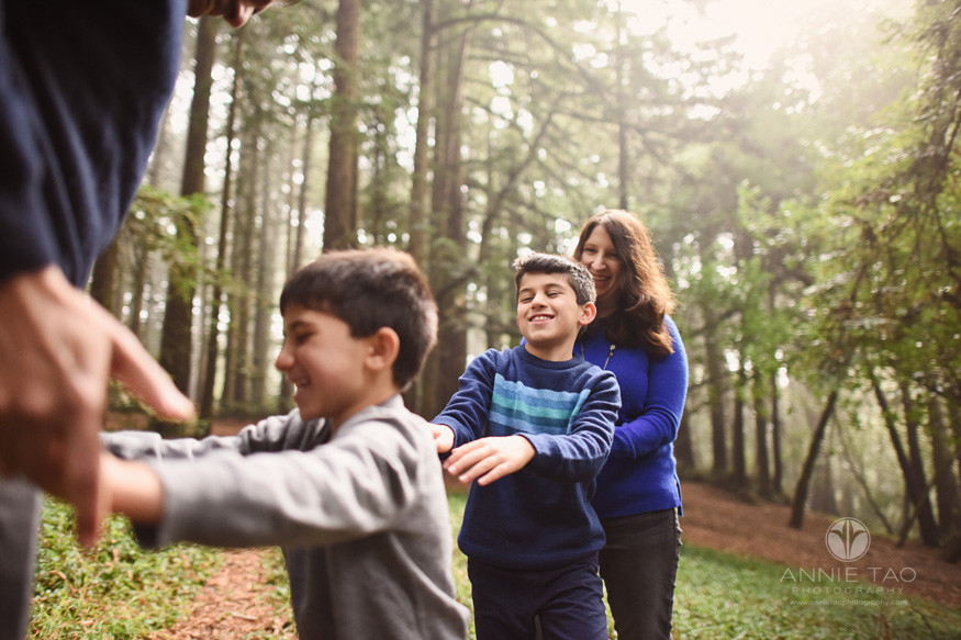 East-Bay-lifestyle-family-photography-mom-and-two-boys-pushing-dad-in-forest