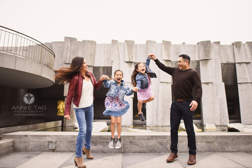 San-Francisco-lifestyle-family-photography-parents-holding-girls-hands-as-they-leap-high