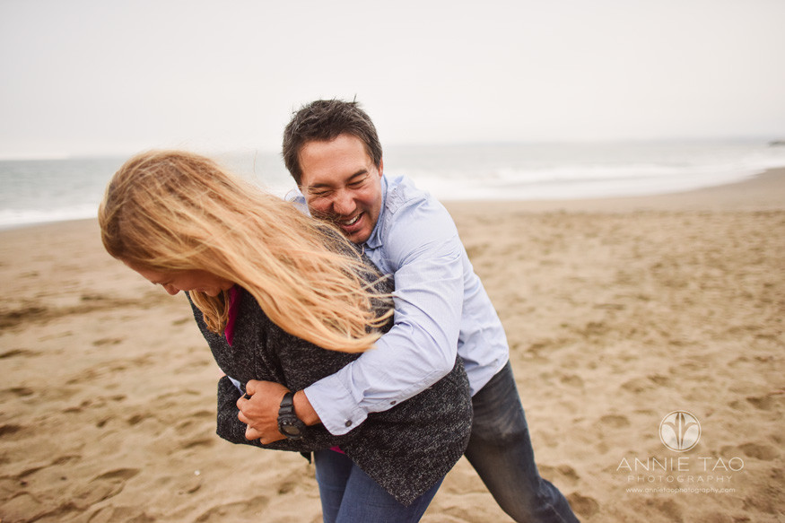 San-Francisco-engagement-photography-playful-man-tackling-woman-with-hug-on-beach