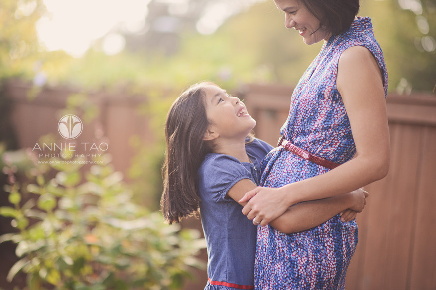 east-bay-lifestyle-family-photography-girl-hugging-mom-tightly-around-waist-and-looks-up-with-sunflare