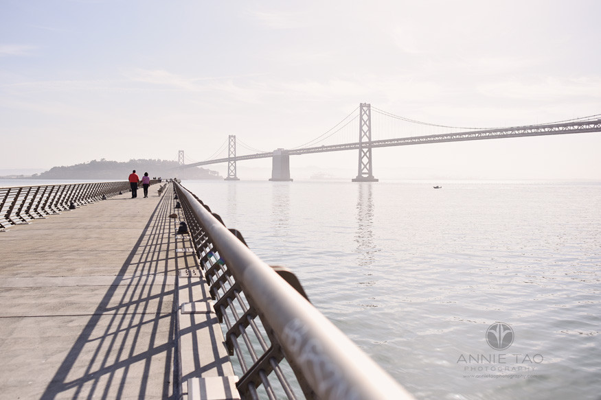 San-Francisco-lifestyle-couple-photography-couple-walking-on-pier-aside-Bay-Bridge