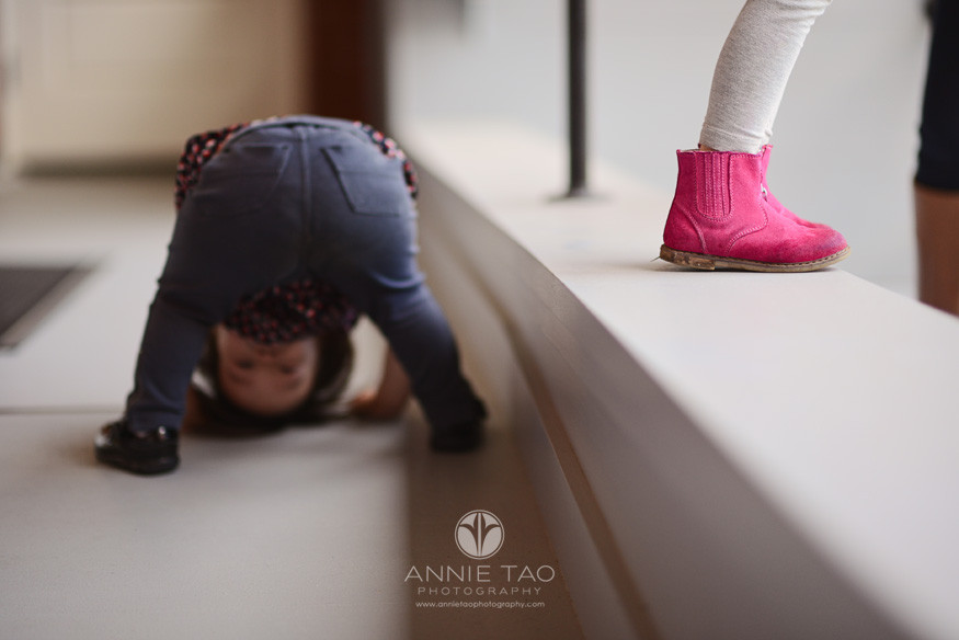 San-Francisco-lifestyle-children-photography-young-girl-standing-with-pink-boots-while-little-sister-is-peeking-through-legs