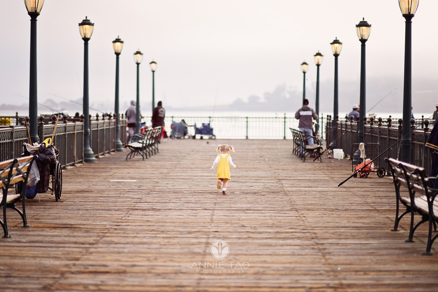 San-Francisco-lifestyle-children-photography-toddler-girl-in-yellow-dress-running-on-pier-surrounded-by-fishermen