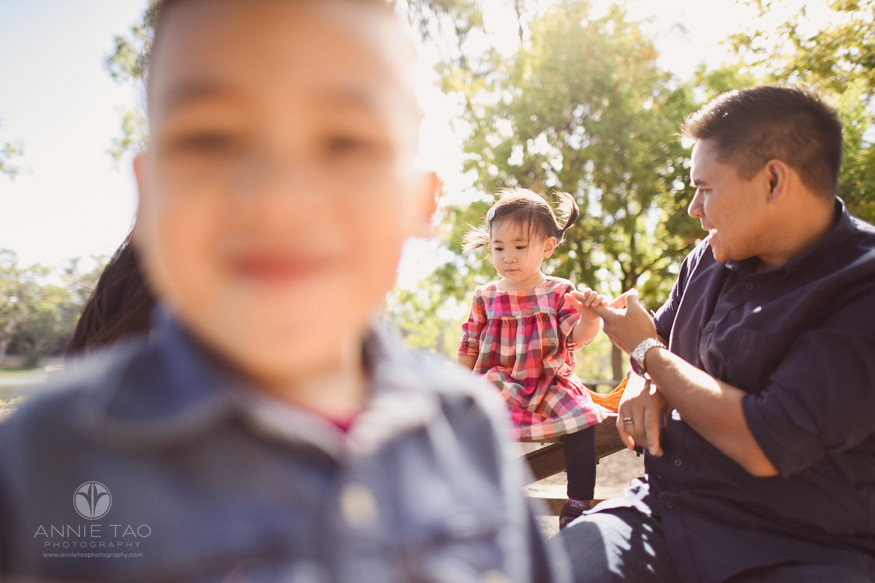 South-Bay-lifestyle-children-photography-toddler-girl-sitting-on-bench-while-boy-too-close-to-photographer