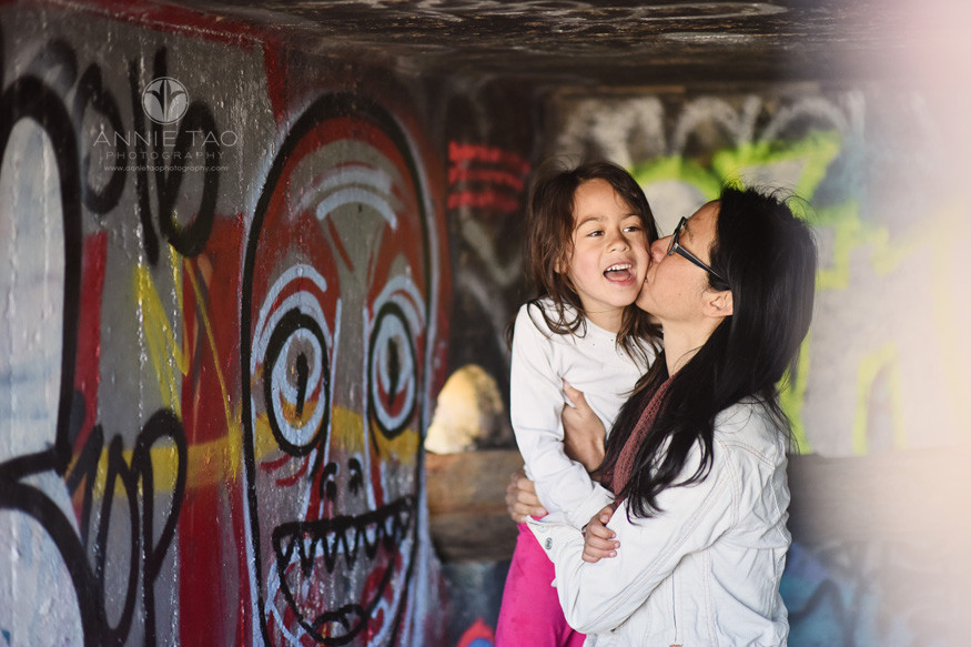 East-Bay-lifestyle-family-photography-mother-kissing-young-daughter-in-graffiti-tunnel
